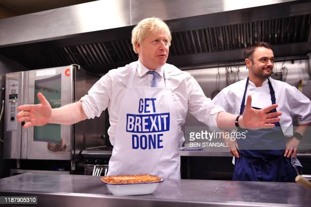 Britain's Prime Minister Boris Johnson prepares a pie at the Red Olive kitchen in Derby, central England on December 11, 2019 while on the campaign...