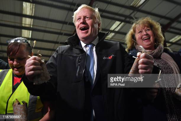 Britain's Prime Minister Boris Johnson reacts after pulling crackers with staff members during a visit to IG Design Group a wrapping paper designer...