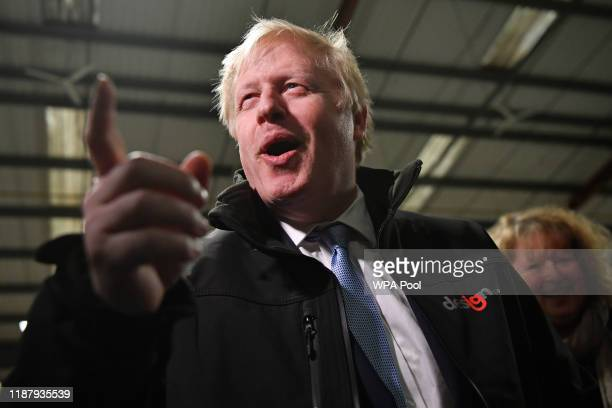 Britain's Prime Minister Boris Johnson reacts after reading the joke found inside one of the crackers during a visit to IG Design Group a wrapping...