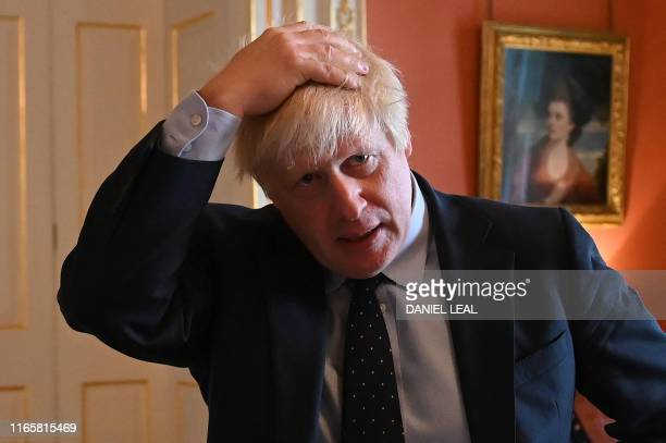 Britain's Prime Minister Boris Johnson reacts as he greets NHS workers as they take afternoon tea inside 10 Downing Street in central London on...
