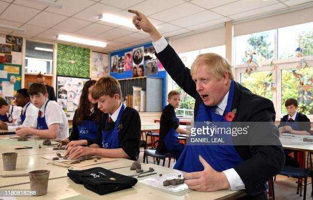 Britain's Prime Minister Boris Johnson reacts as he participates in a school art lesson making a clay figure during a general election campaign visit...