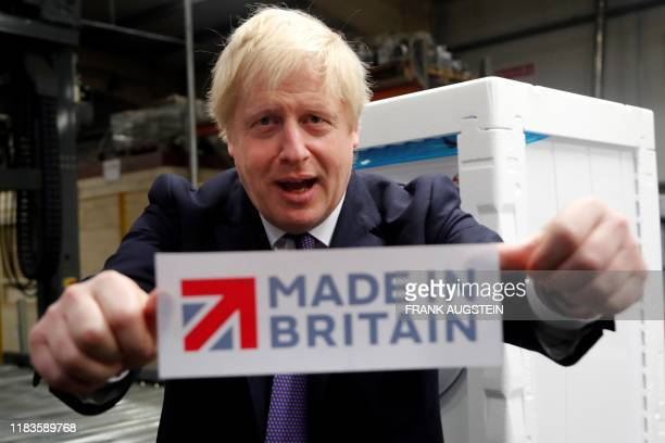 Britain's Prime Minister Boris Johnson reacts as he poses with a made in Britain sticker during his general election campaign visit to Ebac an...