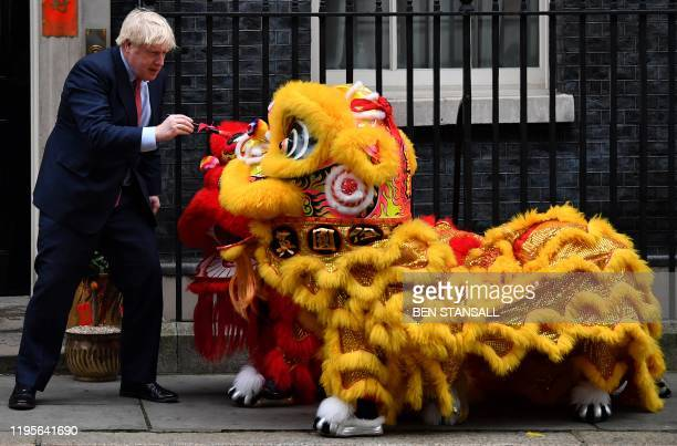 Britain's Prime Minister Boris Johnson reacts as he prepares to paint the eyes on Chinese Lions, as he hosts a Chinese New Year reception at 10...