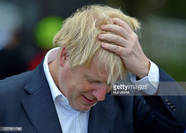 Britain's Prime Minister Boris Johnson reacts as he speaks to local cyclists at the Canal Side Heritage Centre in Beeston, central England, on July...