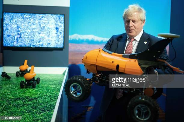 Britain's Prime Minister Boris Johnson reacts as he visits Small Robot Company stand a start up company with plans to reimagine the way technology is...