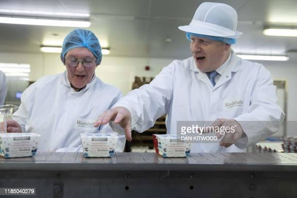 Britain's Prime Minister Boris Johnson reacts during his visit to Cornish Clotted Cream manufacturer Rodda's in Redruth Cornwall on November 27...