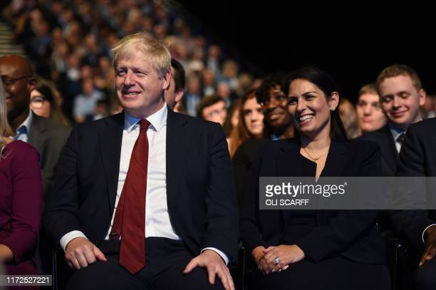 Britain's Prime Minister Boris Johnson reacts seated next to Britain's Home Secretary Priti Patel as he listens to a speech by Britain's Chancellor...