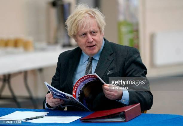 Britain's Prime Minister Boris Johnson reads a magazine as he visits a coronavirus covid-19 vaccination centre in Batley, northern England on...