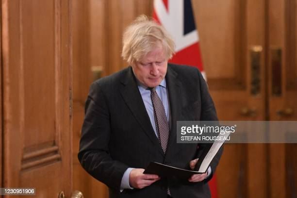 Britain's Prime Minister Boris Johnson reads his notes as he arrives to attend a virtual press conference inside 10 Downing Street in central London...