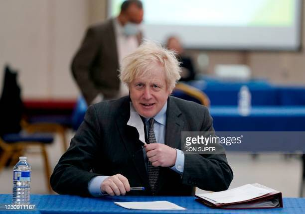 Britain's Prime Minister Boris Johnson removes his face covering during a visit to a coronavirus covid-19 vaccination centre in Batley, northern...