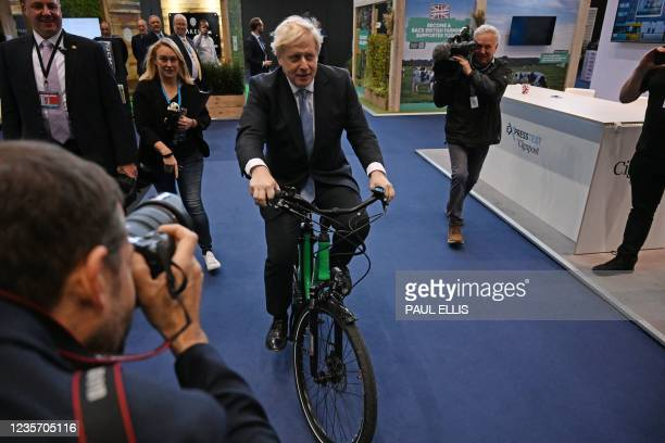 Britain's Prime Minister Boris Johnson rides an e-Bike as he visits the stalls on the third day of the annual Conservative Party Conference at the...