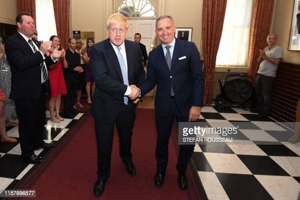Britain's Prime Minister Boris Johnson shakes hands with Cabinet Secretary Mark Sedwill Head of the Civil Service as he is clapped into 10 Downing...