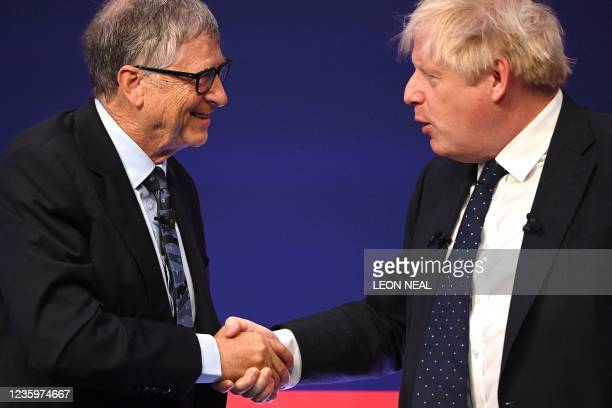 Britain's Prime Minister Boris Johnson shakes hands with Microsoft founder-turned-philanthropist Bill Gates before a discussion on stage during the...