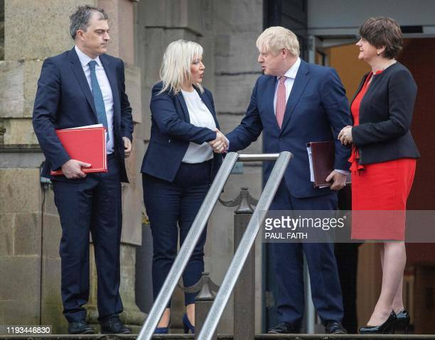 Britain's Prime Minister Boris Johnson shakes hands with Northern Ireland's Deputy First Minister Michelle O'Neill , watched by Britain's Northern...
