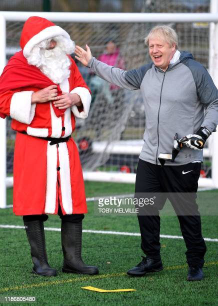 Britain's Prime Minister Boris Johnson shares a joke with a man in Father Christmas costume while on the campaign trail in Cheadle Hulme northwest...