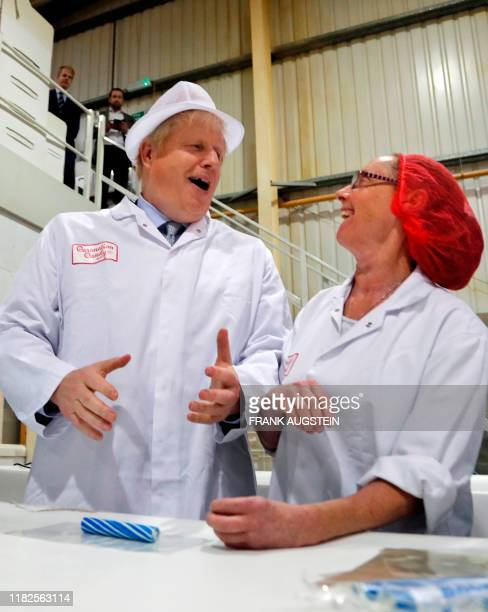 Britain's Prime Minister Boris Johnson shares a joke with a worker as he assists in the production of candy sticks during a visit to Blackpool rock...