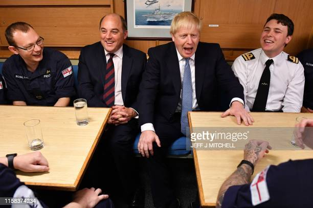 Britain's Prime Minister Boris Johnson shares a joke with Britain's Defence Secretary Ben Wallace and crew members of Vanguardclass submarine HMS...