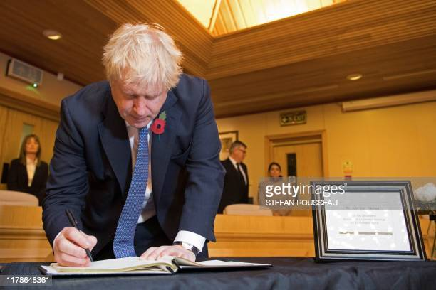 Britain's Prime Minister Boris Johnson signs a book of condolence during a visit to Thurrock Council Offices in Thurrock east of London on October 28...