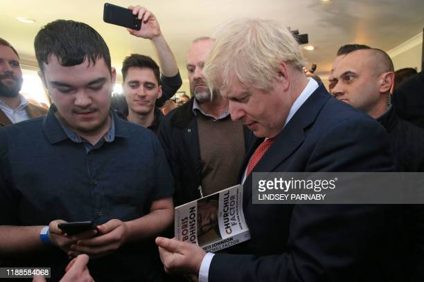 Britain's Prime Minister Boris Johnson signs a copy of one of his books for a supporter during a visit to see newly elected Conservative party MP for...
