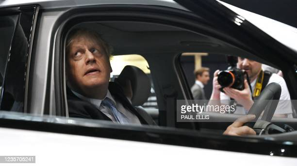 Britain's Prime Minister Boris Johnson sits inside a hydrogen-powered car as he visits the stalls on the third day of the annual Conservative Party...