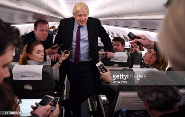 Britain's Prime Minister Boris Johnson speaks to journalists onboard an aircraft bound for Birmingham on December 9 2019 in Birmingham England...
