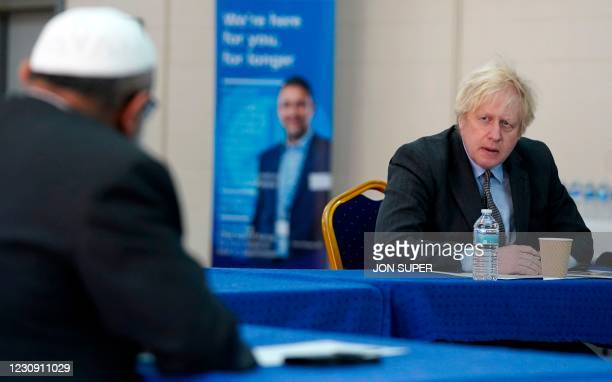 Britain's Prime Minister Boris Johnson speaks to members of staff during a visit to a coronavirus covid-19 vaccination centre in Batley, northern...