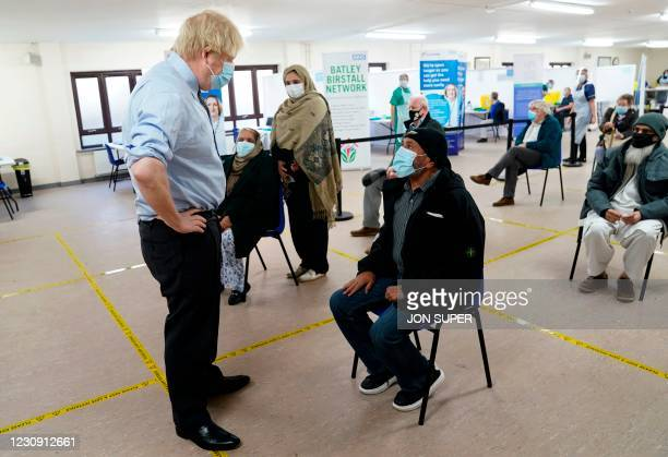 Britain's Prime Minister Boris Johnson speaks to members of the public waiting to receive their vaccine as he visits a coronavirus covid-19...