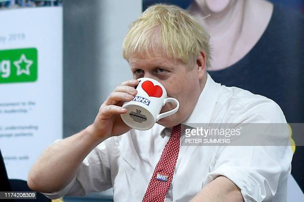 Britain's Prime Minister Boris Johnson speaks to mental health professionals during his visit to Watford General hospital in Watford north of London...