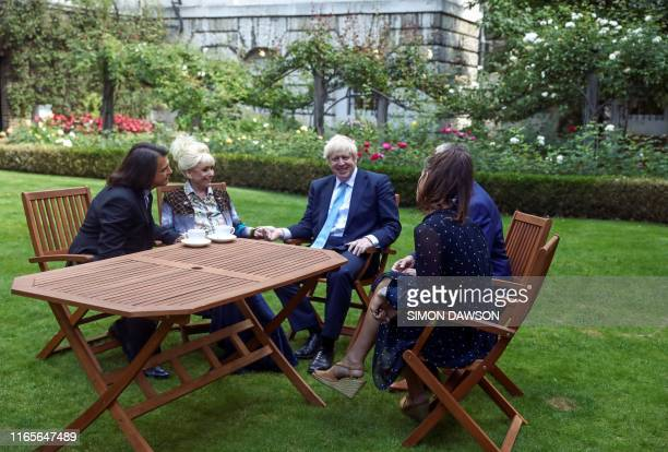 Britain's Prime Minister Boris Johnson speaks with British actress Barbara Windsor and her husband Scott Mitchell after she delivers a petition...