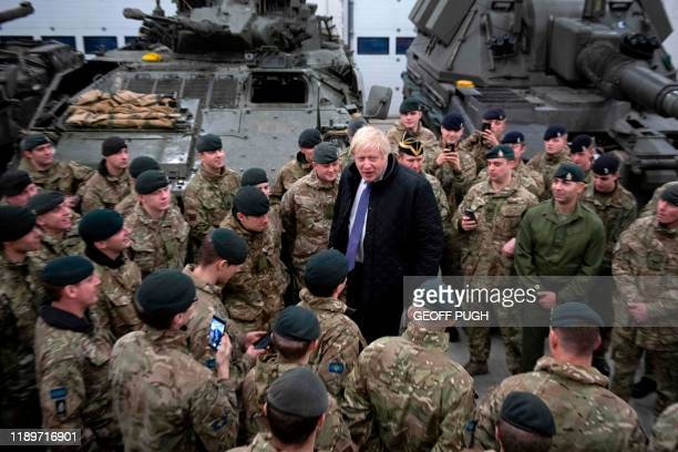 Britain's Prime Minister Boris Johnson speaks with the Queen's Royal Hussars stationed in Estonia at the Tapa military base on December 21 during a...