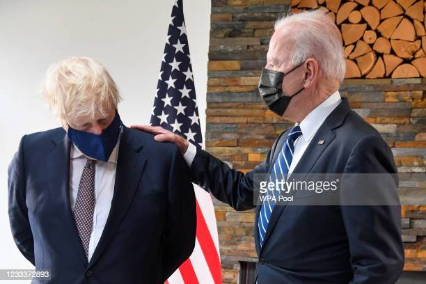 Britain's Prime Minister Boris Johnson speaks with U.S. President Joe Biden look as they look at historical documents and artefacts relating to the...