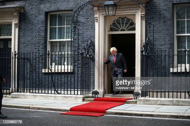 Britain's Prime Minister Boris Johnson stands the doorway of 10 Downing Street to greet French President Emmanuel Macron in central London on June...
