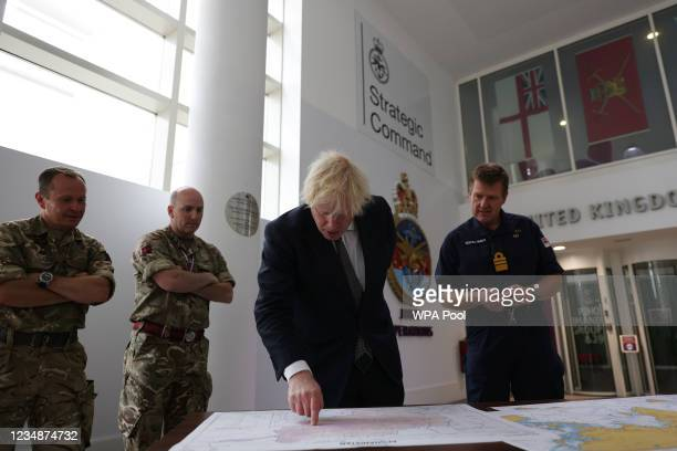 Britain's Prime Minister Boris Johnson stands with Vice Admiral Ben Key as he looks at a map of the Afghanistan region during a visit to Northwood...