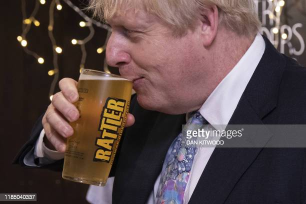 Britain's Prime Minister Boris Johnson takes a sip from a pint of Rattler cider as he visits Healey's Cornish Cyder Farm in Callestick Cornwall on...