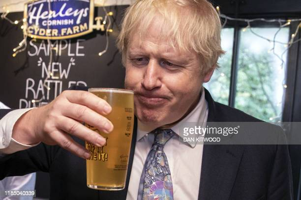 Britain's Prime Minister Boris Johnson takes a sip from a pint of Rattler cider as he visits Healey's Cornish Cyder Farm in Callestick, Cornwall on...