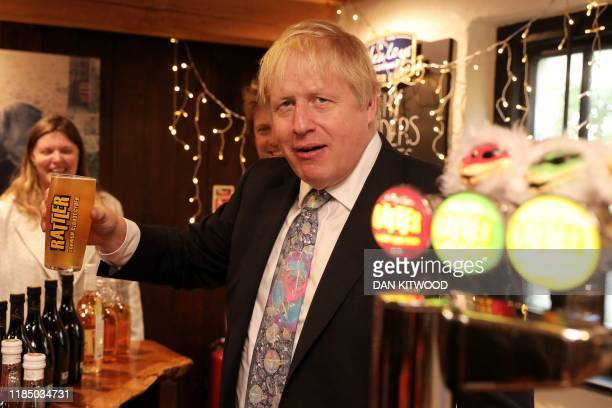 Britain's Prime Minister Boris Johnson takes a sip of cider as he visits Healey's Cornish Cyder Farm in Callestick, Cornwall on November 27 during...
