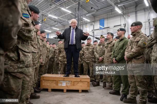 TOPSHOT Britain's Prime Minister Boris Johnson talks with British troops stationed in Estonia at the Tapa military base on December 21 during a...
