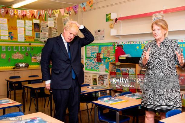 Britain's Prime Minister Boris Johnson talks with head teacher Bernadette Matthews in a classroom as he visits St Joseph's Catholic Primary School in...