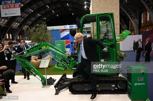 Britain's Prime Minister Boris Johnson tries an electric tractor at a stall on the third day of the annual Conservative Party Conference at the...