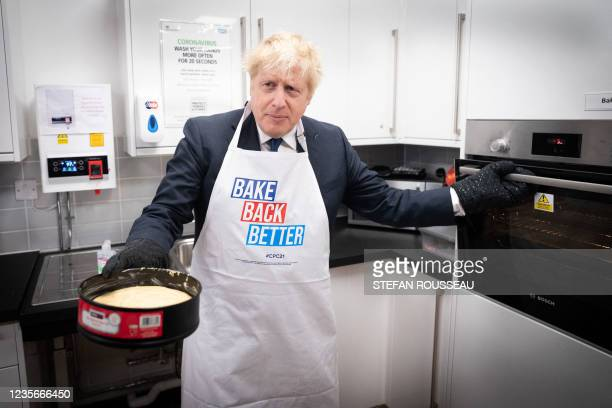Britain's Prime Minister Boris Johnson tries his hand at baking during a visit to the HideOut Youth Zone on the morning of the first day of the...