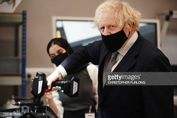 Britain's prime minister Boris Johnson uses a power tool during a visit to BAE Systems at Warton Aerodrome in Preston, northwest England, on March...
