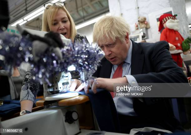 Britain's Prime Minister Boris Johnson uses a sewing machine during a Conservative Party general election campaign visit to John Smedley Mill in...