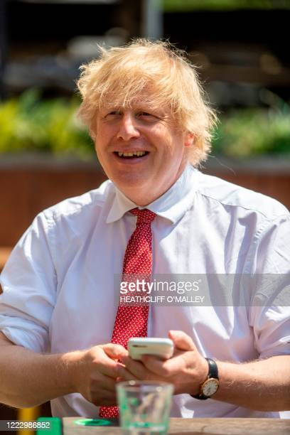 Britain's Prime Minister Boris Johnson uses his smartphone as he visits Pizza Pilgrims in West India Quay, London Docklands on June 26, 2020 as the...