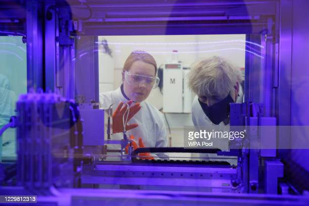 Britain's Prime Minister Boris Johnson views a PCR diagnostics machine with biomedical scientist Jodie Owen in a laboratory during a visit to the...