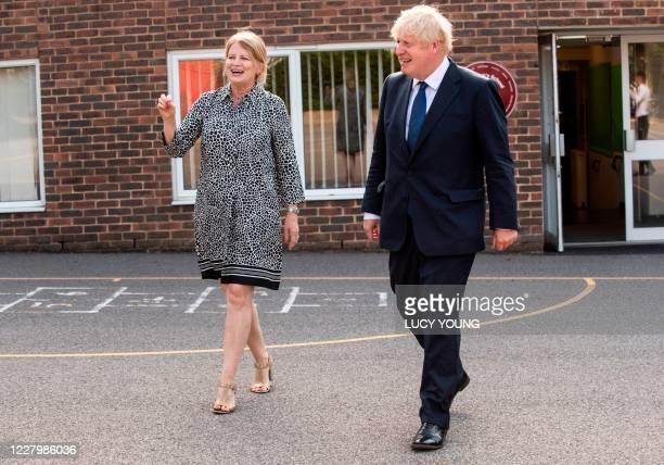 Britain's Prime Minister Boris Johnson walks in the playground with head teacher Bernadette Matthews as he visits St Joseph's Catholic Primary School...