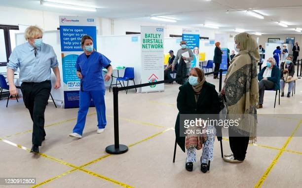 Britain's Prime Minister Boris Johnson walks past members of the public waiting to receive their vaccine as he visits a coronavirus covid-19...