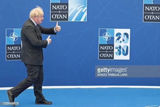 Britain's Prime Minister Boris Johnson walks towards NATO Secretary General during the strat of the NATO summit at the North Atlantic Treaty...