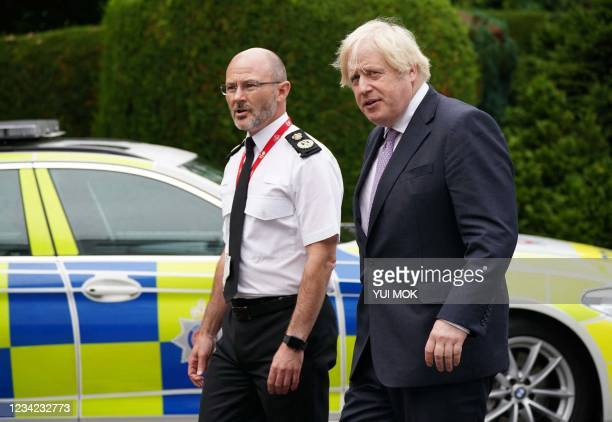 Britain's Prime Minister Boris Johnson walks with Chief Constable Gavin Stephens during a visit to Surrey Police headquarters in Guildford, south...