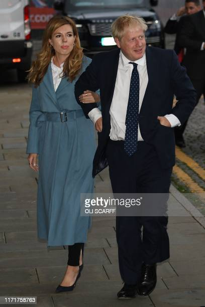 Britain's Prime Minister Boris Johnson walks with his partner Carrie Symonds as they arrive at The Midland near the Manchester Central convention...