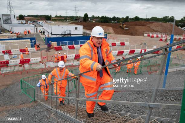 Britain's Prime Minister Boris Johnson walks with workers during his visit to the Solihull Interchange construction site for the HS2 high-speed...